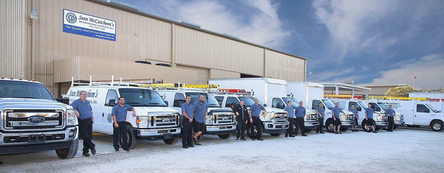 Sean McCutcheon's Air Conditioning and Heating service technicians in front of their trucks